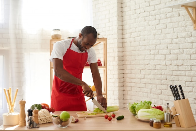African american man in apron slices celery in kitchen. Premium Photo