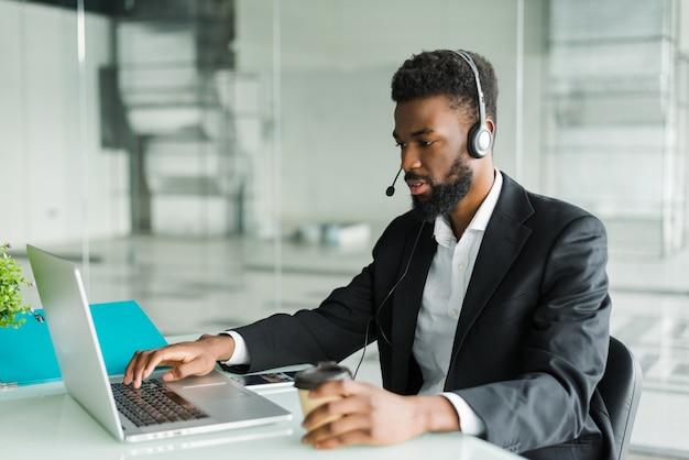 Operatore del servizio clienti uomo afroamericano con la cuffia avricolare a mani libere che lavora nell'ufficio. Foto Gratuite
