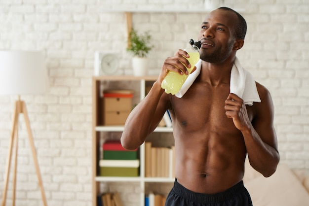 African american man drinks juice from bottle after training Premium Photo