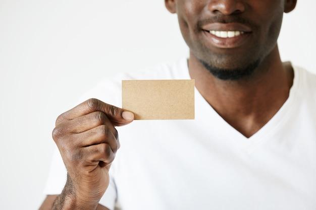 Афро-американский мужчина держит коричневую пустую визитную карточку Бесплатные Фотографии