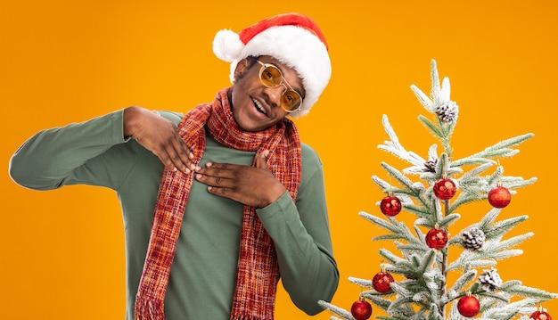 Афро-американский мужчина в новогодней шапке и шарфе на шее, держась за руки на груди, счастлив и позитивен, чувствуя благодарность, стоя рядом с елкой над оранжевой стеной Бесплатные Фотографии