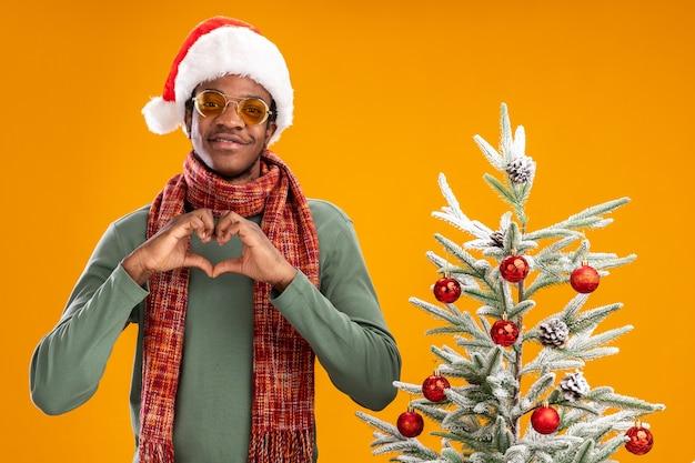 Афро-американский мужчина в новогодней шапке и шарфе на шее, делая жест сердца с пальцами, улыбаясь, стоит рядом с рождественской елкой на оранжевом фоне Бесплатные Фотографии