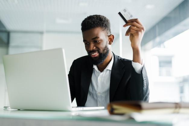 Афро-американский мужчина оплаты кредитной картой онлайн при совершении заказов через мобильный интернет, совершая транзакции с помощью мобильного банковского приложения. Бесплатные Фотографии