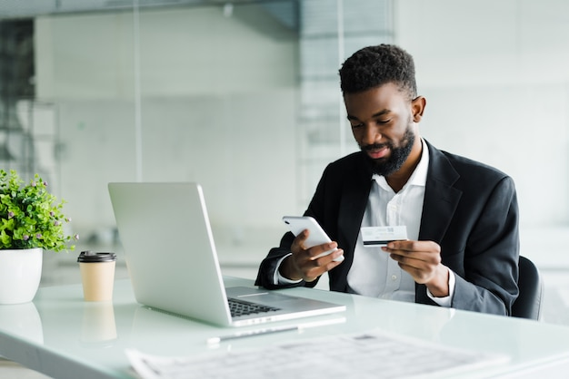 African american man paying with credit card online while making orders via mobile internet making transaction using mobile bank application. Free Photo