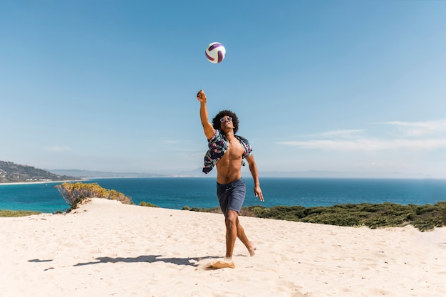 African american man playing with ball on beach Free Photo