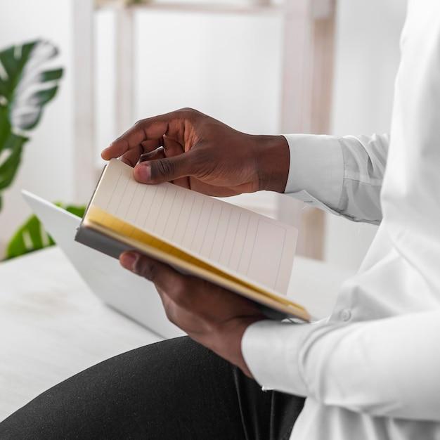 彼のノートのクローズアップを読んでアフリカ系アメリカ人の男 無料写真