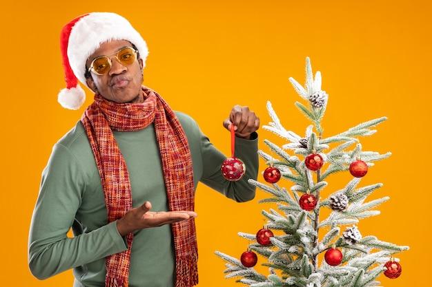 Uomo afroamericano in cappello della santa e sciarpa intorno alla sfera della tenuta del collo che lo presenta guardando dispiaciuto in piedi accanto a un albero di natale su sfondo arancione Foto Gratuite