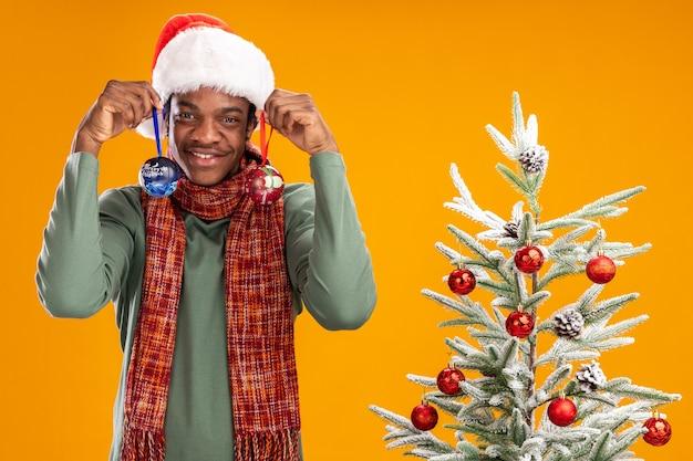 Uomo afroamericano in cappello della santa e sciarpa intorno al collo che tengono le palle di natale in piedi felice e positivo accanto a un albero di natale sopra fondo arancio Foto Gratuite
