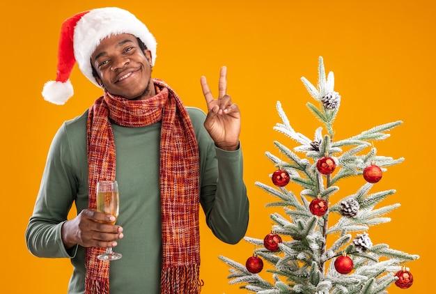 Uomo afroamericano in santa cappello e sciarpa intorno al collo tenendo un bicchiere di champagne sorridendo allegramente mostrando v-segno accanto all'albero di natale su sfondo arancione Foto Gratuite