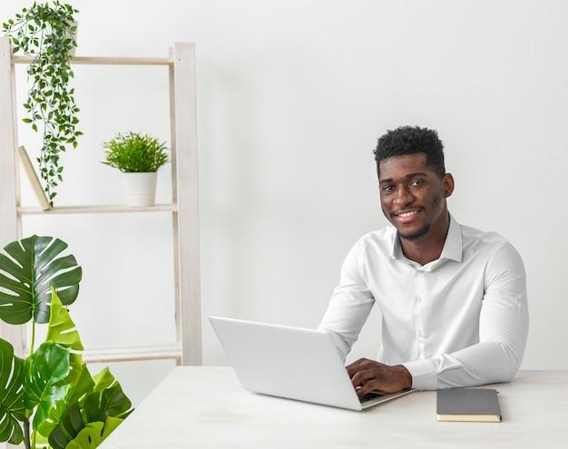 机に座って笑顔のアフリカ系アメリカ人の男 無料写真
