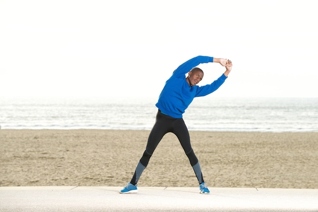 African american man stretching muscles at the beach Premium Photo