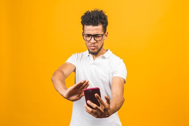 Афро-американский мужчина с помощью смартфона подчеркнул, сердит и разочарован Premium Фотографии