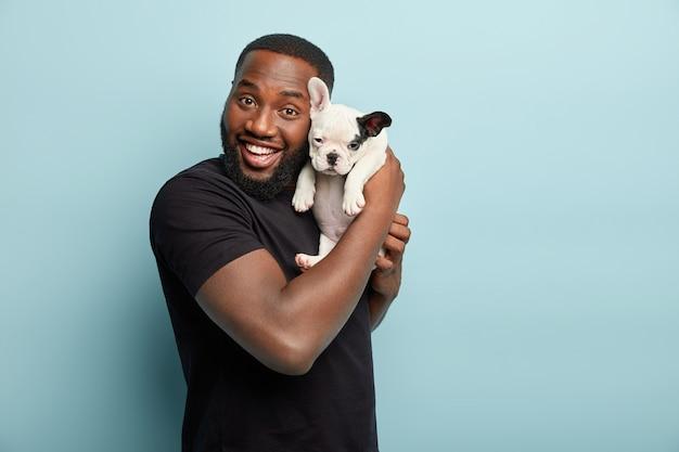 검은 티셔츠를 입고 작은 개를 들고 아프리카 계 미국인 남자 무료 사진