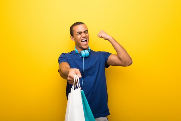 African american man with blue t-shirt on yellow background holding a lot of shopping bags Premium Photo