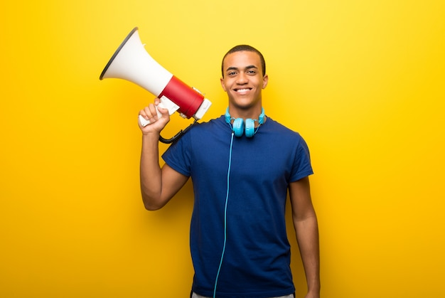 African american man with blue t-shirt on yellow background holding a megaphone Premium Photo