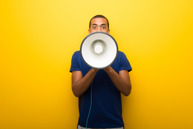 African american man with blue t-shirt on yellow background shouting through Premium Photo