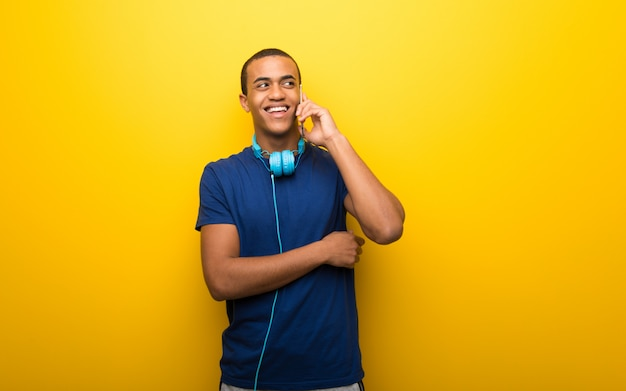 African american man with blue t shirt on yellow wall keeping a conversation with the mobile phone with someone Premium Photo