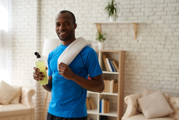 African american man with bottle is having rest. Premium Photo