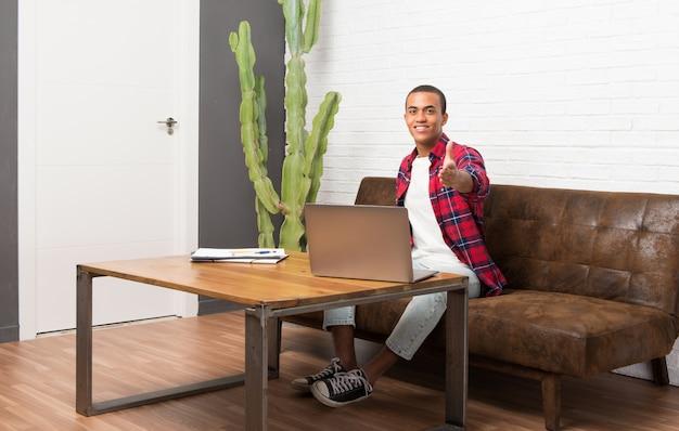 リビングルームでラップトップを持つアフリカ系アメリカ人の男性 Premium写真