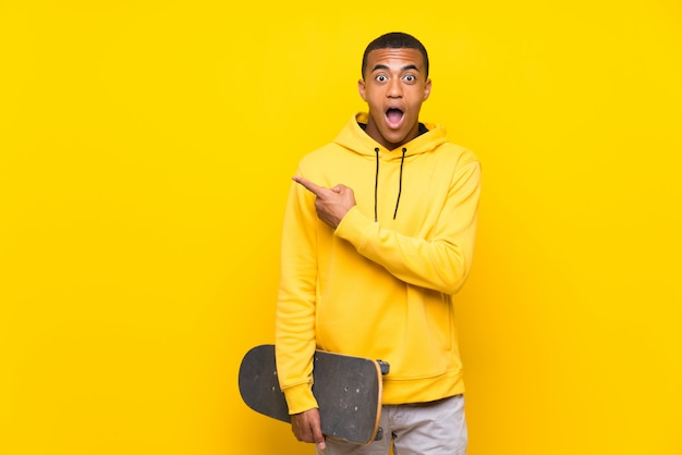 African american skater man surprised and pointing side Premium Photo