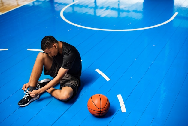 African american teenage boy tying his shoe laces on a basketball court Free Photo