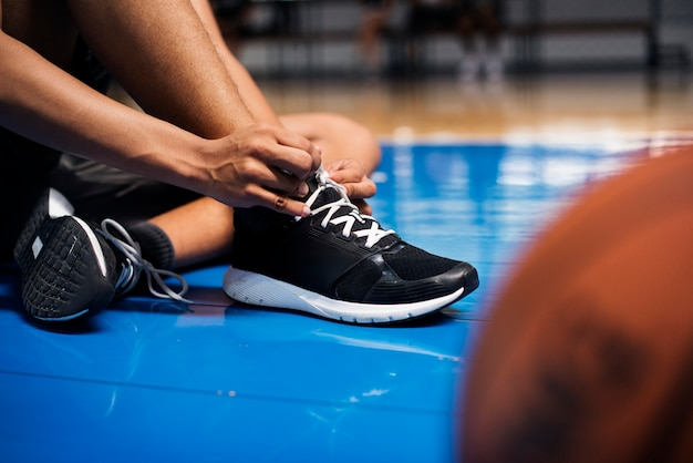 African american teenage boy tying his shoe laces on a basketball court Premium Photo