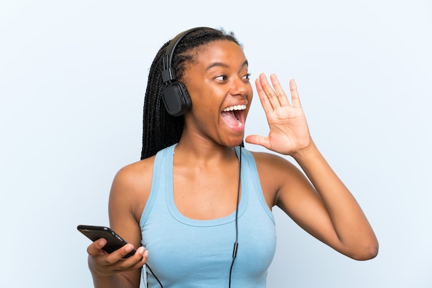 African american teenager girl with long braided hair listening music with a mobile shouting with mouth wide open Premium Photo