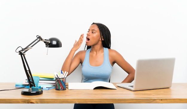 African american teenager student girl with long braided hair in her workplace yawning Premium Photo