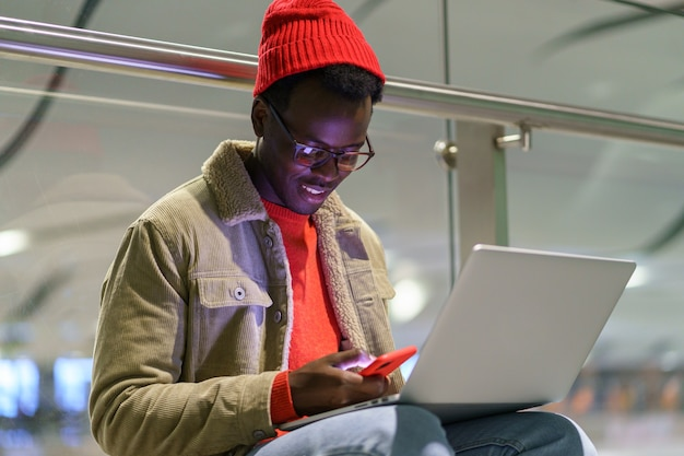 African american traveler millennial man resting and sitting on the floor in airport using cellphone Premium Photo