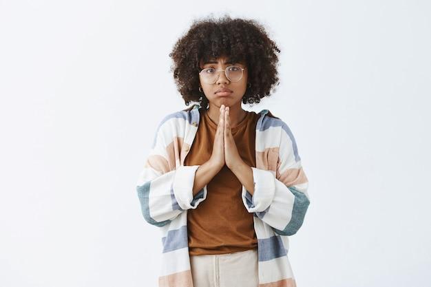 Афроамериканка в беде, мрачная и расстроенная, держась за руки в молитве, хмурясь и дуясь, прося об одолжении или моля о помощи Бесплатные Фотографии