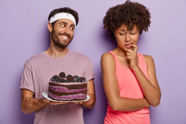 La donna afroamericana tiene il dito sulla bocca, prova la tentazione mentre guarda la deliziosa torta ai mirtilli Foto Gratuite