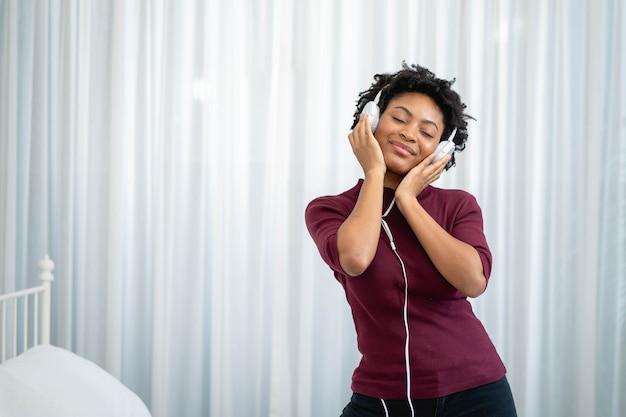 Афро-американская женщина слушает музыку в наушниках в гостиной Premium Фотографии