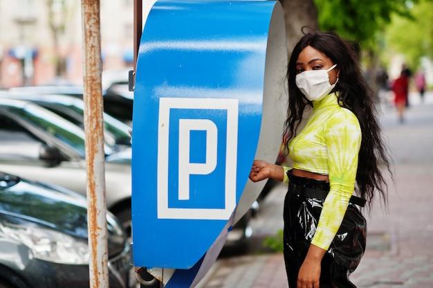 Афро-американских женщина позирует с лицевой маской для защиты от инфекций от бактерий, вирусов и эпидемий, используя парковку терминала. Premium Фотографии