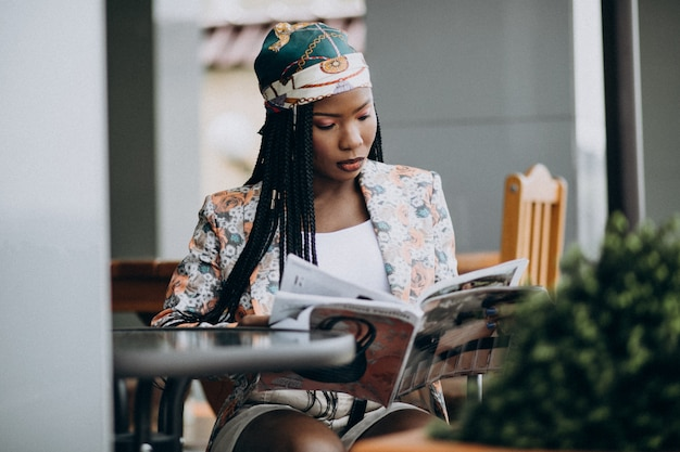 African american woman reading magazine in a cafe Free Photo