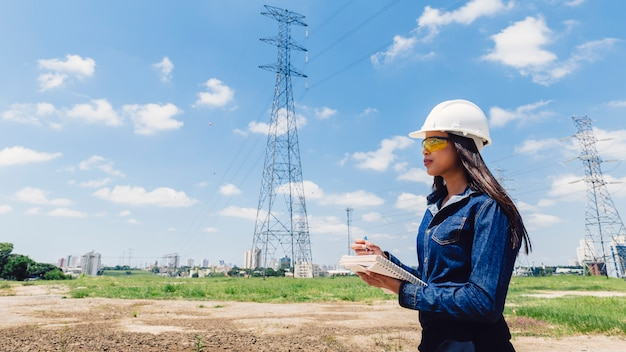African american woman in safety helmet taking notes near high voltage line Free Photo