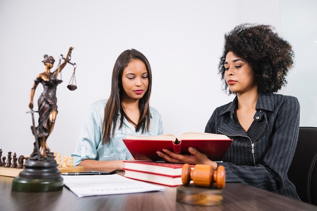African american woman showing book to lady at table with document, statue and chess Free Photo