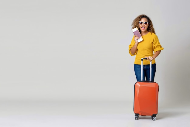African american woman tourist with luggage holding passport and boarding pass Premium Photo