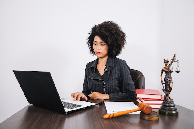 African american woman using laptop at table near smartphone, books, document and statue Free Photo