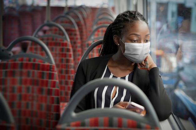 Афро-американская женщина в маске в автобусе во время поездки на общественном транспорте в новой нормальной обстановке Бесплатные Фотографии