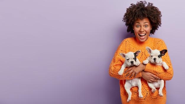 강아지를 들고 주황색 스웨터를 입고 아프리카 계 미국인 여자 무료 사진