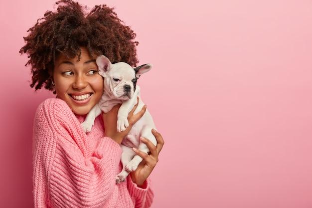 Donna afro-americana che indossa un maglione rosa che tiene cucciolo Foto Gratuite