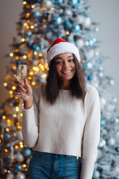 집에서 샴페인 잔 아프리카 계 미국인 여자. 크리스마스 축하 무료 사진