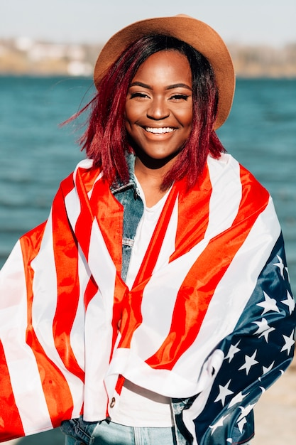 African american woman wrapping in us flag Free Photo