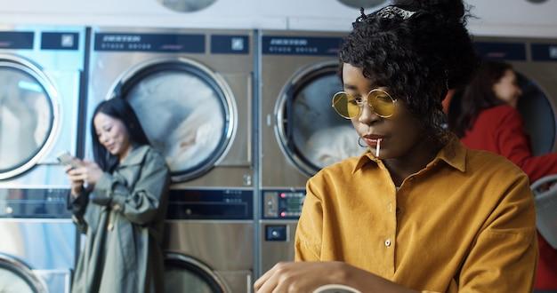 ランドリーサービスルームに立地する黄色のメガネでアフリカ系アメリカ人の美しい少女。公共のコインランドリーで服が洗われるのを待っている間ロリーポップ読書雑誌を持つ女性。 Premium写真