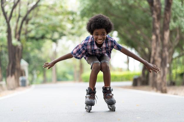 屋外でローラースケートやローラーブレードに乗ってアフリカ系アメリカ人の少年。 Premium写真