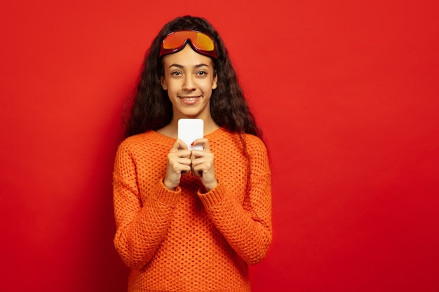 African-american young brunette woman's portrait in ski mask on red studio background. concept of human emotions, facial expression, sales, ad, winter sport and holidays. chatting with phone. Free Photo