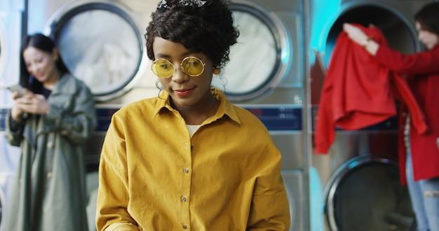 アフリカ系アメリカ人の若いきれいでスタイリッシュな女の子のランドリーサービスルームに立っているとファッションジャーナルのページをめくって黄色のメガネ。服が洗われるのを待っている間雑誌を読んでいる女性。 Premium写真