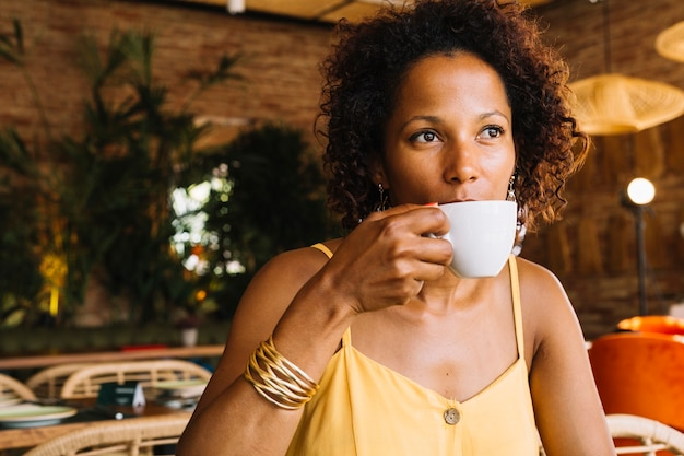 African-american young woman drinking coffee from white cup Free Photo