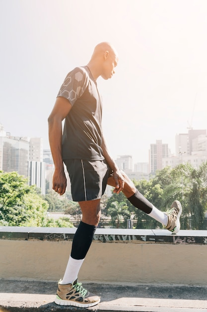 African athlete young man stretching his leg on rooftop in the city Free Photo