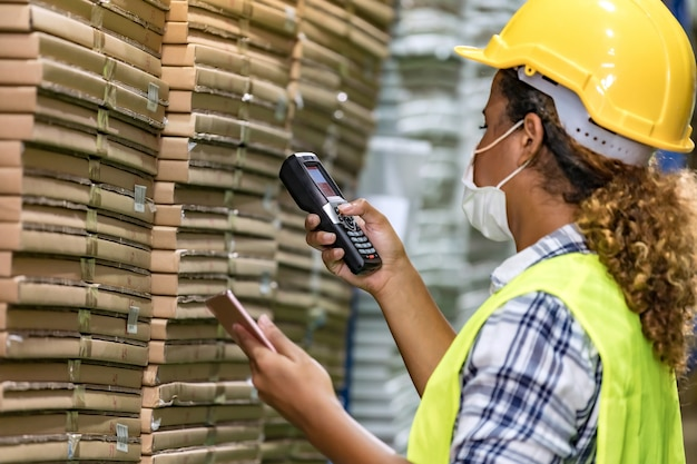 African black warehouse worker with face mask checking goods use digital tablet and barcode scanner, she wear face mask prevent from covid-19 after factory reopen. Premium Photo
